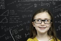 Smart young girl stood infront of a blackboard Royalty Free Stock Image