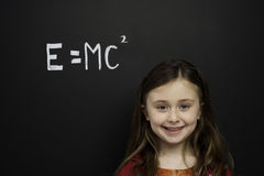 Smart young girl stood infront of a blackboard Royalty Free Stock Photo