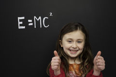 Smart young girl stood infront of a blackboard Royalty Free Stock Images