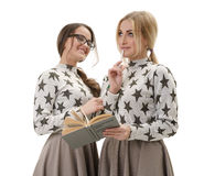 Smart young girls posing in studio with a book Stock Photos