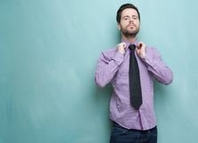Smart young guy adjusting his necktie Royalty Free Stock Images