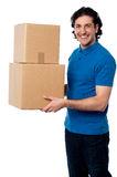 Smart young man carrying boxes Royalty Free Stock Image