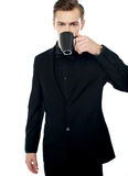 Smart young man drinking coffee in black cup Royalty Free Stock Image