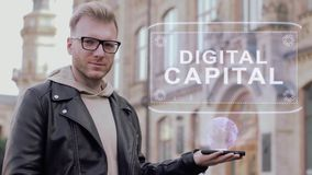 Smart young man with glasses shows a conceptual hologram Digital capital. Student in casual clothes with future technology mobile screen on university stock video footage