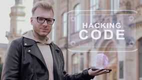 Smart young man with glasses shows a conceptual hologram Hacking code. Student in casual clothes with future technology mobile screen on university background stock footage
