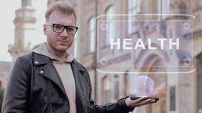 Smart young man with glasses shows a conceptual hologram Health. Student in casual clothes with future technology mobile screen on university background stock video