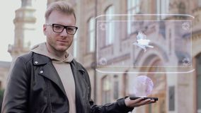 Smart young man shows hologram eagle. Smart young man with glasses shows a conceptual hologram particle eagle. Student in casual clothes with future technology stock video footage