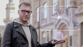 Smart young man with glasses shows a conceptual hologram satellite. Student in casual clothes with future technology mobile screen on university background stock video