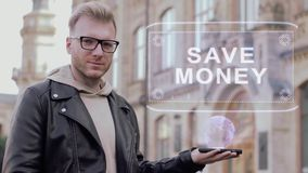 Smart young man with glasses shows a conceptual hologram Save money. Student in casual clothes with future technology mobile screen on university background stock footage