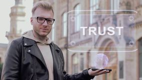 Smart young man with glasses shows a conceptual hologram Trust. Student in casual clothes with future technology mobile screen on university background stock video footage