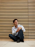 Smart young man sitting on floor and looking away Royalty Free Stock Image
