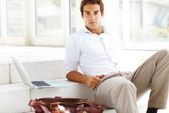 Smart young man sitting on stairs with laptop Royalty Free Stock Image