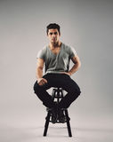 Smart young man sitting on stool Royalty Free Stock Photography