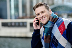 Smart young man talking via cell phone Stock Images