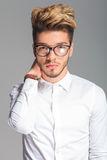 Smart young man wearing frames and touching his neck Royalty Free Stock Image