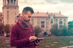 Smart young man works on tablet computer outdoors in urban public space stock image