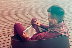 Smart young man works on tablet computer outdoors in urban public space royalty free stock images