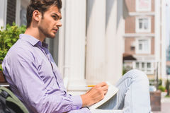 Smart young man writing into notebook. Pensive male student is studying outdoors. He is making notes into writing-pad with seriousness. Guy is sitting on bench Royalty Free Stock Image