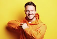 Smart young smiling man standing against yellow background royalty free stock photography