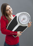Smart young woman holding her scale with satisfaction for weight control Stock Photos
