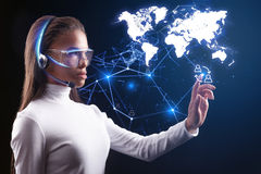 Smart young woman using future network technology. Creating human communication. Serious futuristic female operator is connecting people around the world by Stock Photos