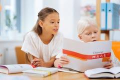 Smarta barn som tillsammans lär kines hemma royaltyfria foton
