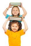 Smarta flickor med högen av böcker Royaltyfria Bilder
