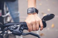 Smarta klockor hjälper cyklisten på gatan, hand i clo arkivfoton