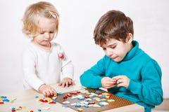 Smarta nätta ungar som spelar med den bildande mosaiken royaltyfri fotografi