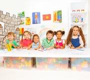 Smarta små ungar som lär bokstäver och läsning Arkivfoton