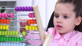 Smartest little girl in the office conducts raschty using colored wooden abacus stock video footage