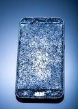 Smarthphone with crushed screen into pieces on a blue reflective surface, studio shot / Destroied equipment. Smarthphone with crushed screen into pieces on a royalty free stock photography