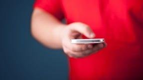 Smarthphone della tenuta del giovane a disposizione Fotografie Stock