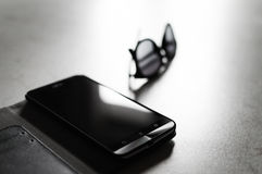 Smarthphone & Sunglasses. Commercial image that depicts a smartphone and a pair of glasses. A narrow frame and backlight that intensity and contrast objects Royalty Free Stock Photo