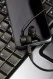 Smarthpone sobre o keybaord do portátil Fotos de Stock