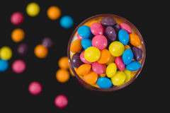 Smarties in jar. Spilling our, on black background Royalty Free Stock Photography