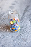 Smarties in a jar. Sweet color chocolate smarties in a glass jar on a slate background Stock Image