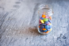 Smarties in a jar. Sweet color chocolate smarties in a glass jar on a slate background Royalty Free Stock Photos