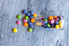 Smarties in a jar. Sweet color chocolate smarties on grey slate and glass jar placed near the pile Royalty Free Stock Images