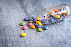 Smarties in a jar. Sweet color chocolate smarties on grey slate and glass jar placed near the pile Stock Photography