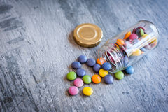 Smarties in a jar. Sweet color chocolate smarties on grey slate and glass jar placed near the pile Royalty Free Stock Photos