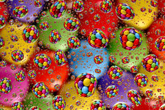 Smarties through Water Droplets (1). Colorful, aligned smarties, reflected through random water droplets Royalty Free Stock Photo