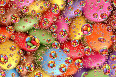 Smarties through Water Droplets (2). A pile of colorful smarties reflected through water droplets Royalty Free Stock Image