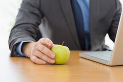 Smartly dressed businessman with laptop and apple at office Stock Photography