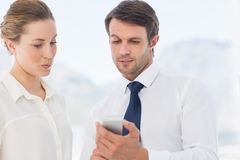 Smartly dressed colleagues looking at mobile phone Stock Photo