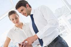 Smartly dressed colleagues looking at mobile phone Royalty Free Stock Photos