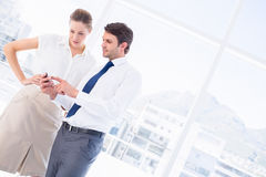 Smartly dressed colleagues looking at mobile phone Stock Image