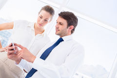 Smartly dressed colleagues looking at mobile phone Stock Photos