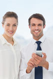 Smartly dressed colleagues with a mobile phone Royalty Free Stock Image