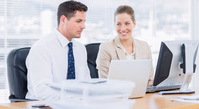 Smartly dressed colleagues using computer Stock Photos